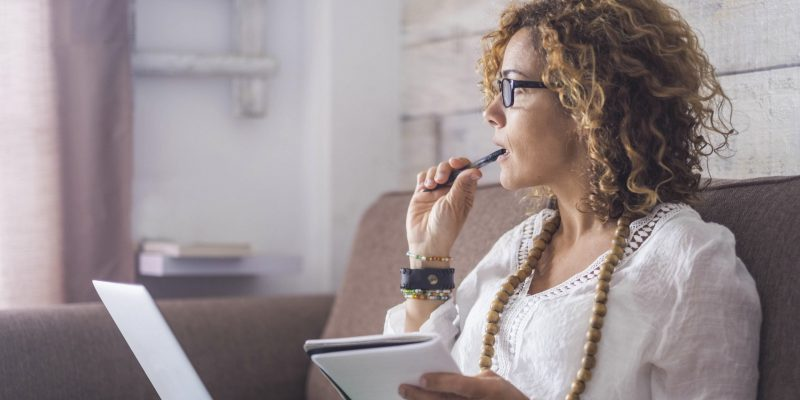 Woman working from home deciding to invest in a franchise
